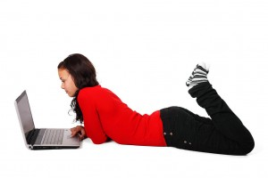 11706-a-beautiful-girl-lying-on-the-floor-with-a-laptop-isolated-on-a-white-b-pv