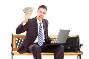Happy businessman with laptop sitting on a wooden bench and holding US dollars isolated on white background
